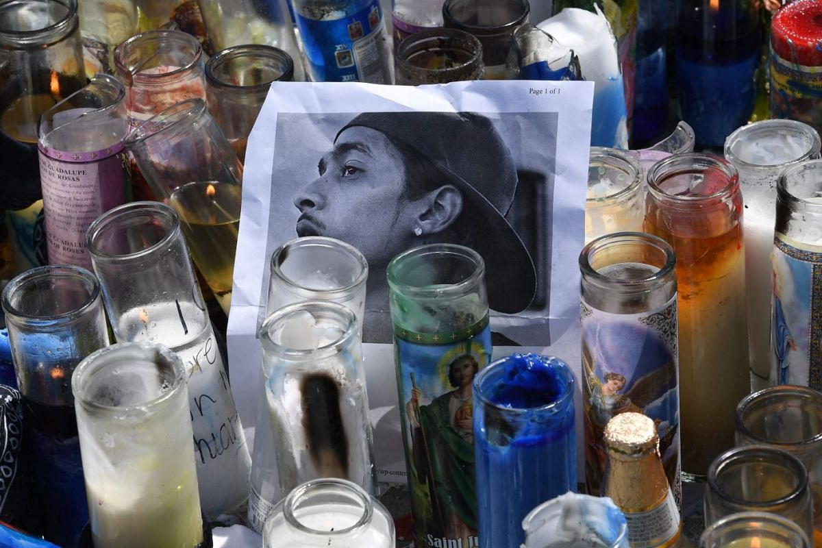 A photo of Nipsey Hussle and candles placed at the makeshift memorial outside the late rapper's shop.