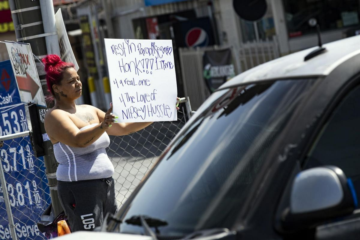 A woman holding a poster in remembrance of rapper Nipsey Hussle in Los Angeles, California.