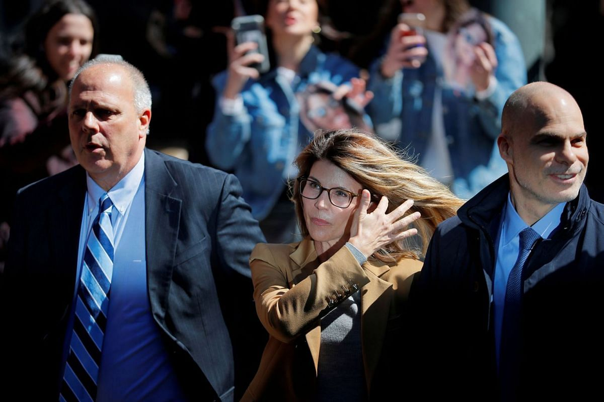 Actor Lori Loughlin, facing charges in a nationwide college admissions cheating scheme, is escorted to federal court in Boston, Massachusetts, U.S., April 3, 2019. PHOTO: REUTERS