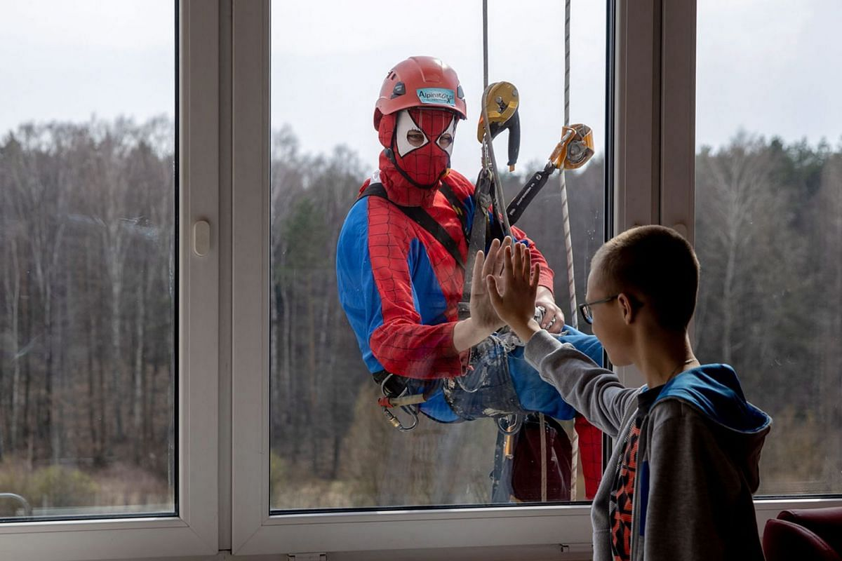 A photo issued on April 4, 2019, shows a patient and a window cleaner in a superhero costume greeting each other at the John Paul II Upper Silesian Child Health Centre in Katowice, Poland on March 3, 2019. PHOTO: EPA-EFE