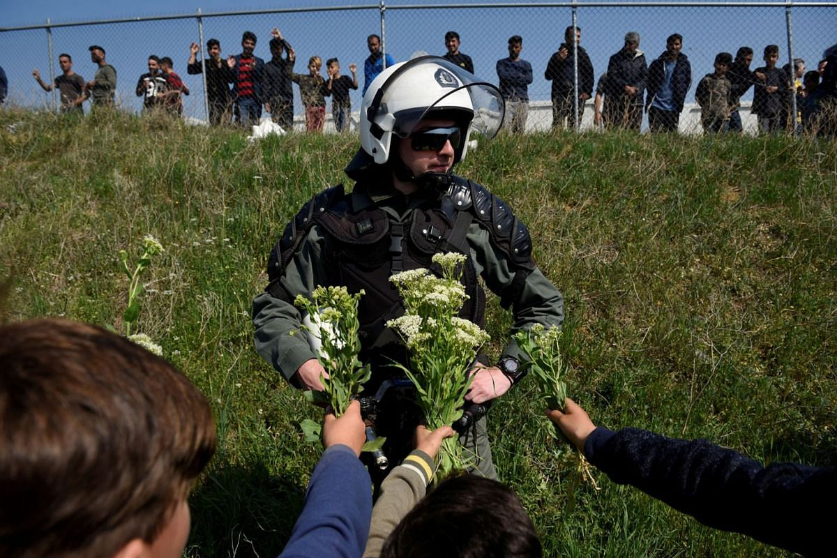 Migrant children offer flowers to a riot police officer next to a camp in the town of Diavata in northern Greece, April 4, 2019. PHOTO: REUTERS