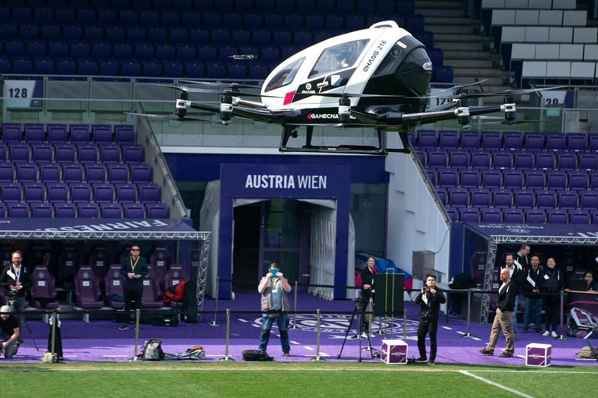 """Journalists onboard of an Air Taxi EHANG 216 take a short flight during a press preview of FACC AG on """"Urban Air Mobility"""" at Generali Arena in Vienna, Austria on April 4, 2019. - China's EHANG and Austrian FACC AG plan to produce 300 Taxi drones by"""