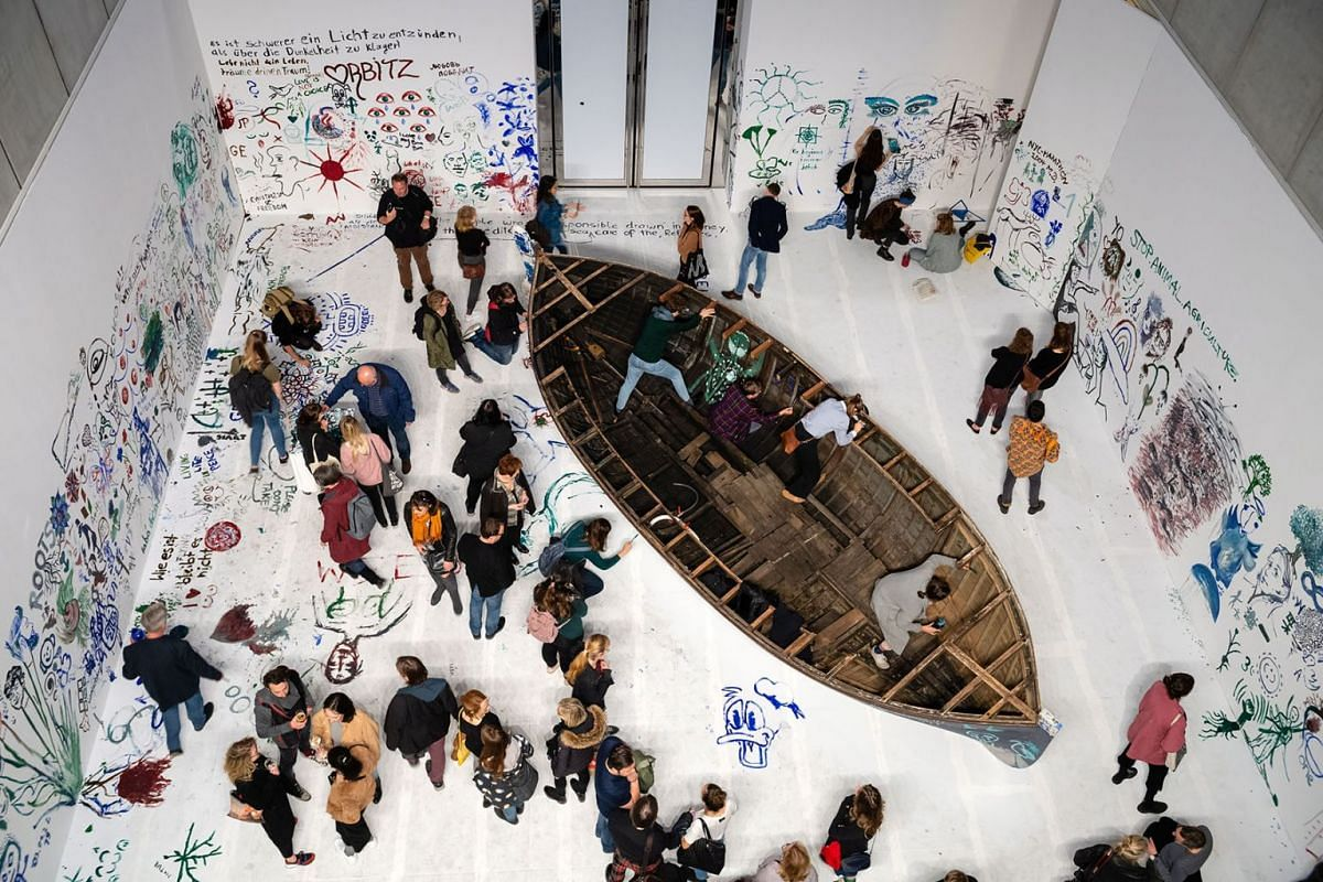 """Visitors at the work """"Add colour painting (Refugee boat)"""" of the Japanese-American artist Yoko Ono during the opening of the exhibition 'PEACE is POWER' in the Museum of the Fine Arts (Museum der bildenden Kuenste) in Leipzig, Germany, April 3, 2019."""