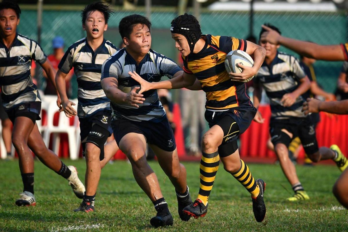 Hunter Alexander Hogson Kusmuljadi (with ball) from ACS(I) is swarmed by his St Andrew's opponents in the B division Boys Rugby Final.