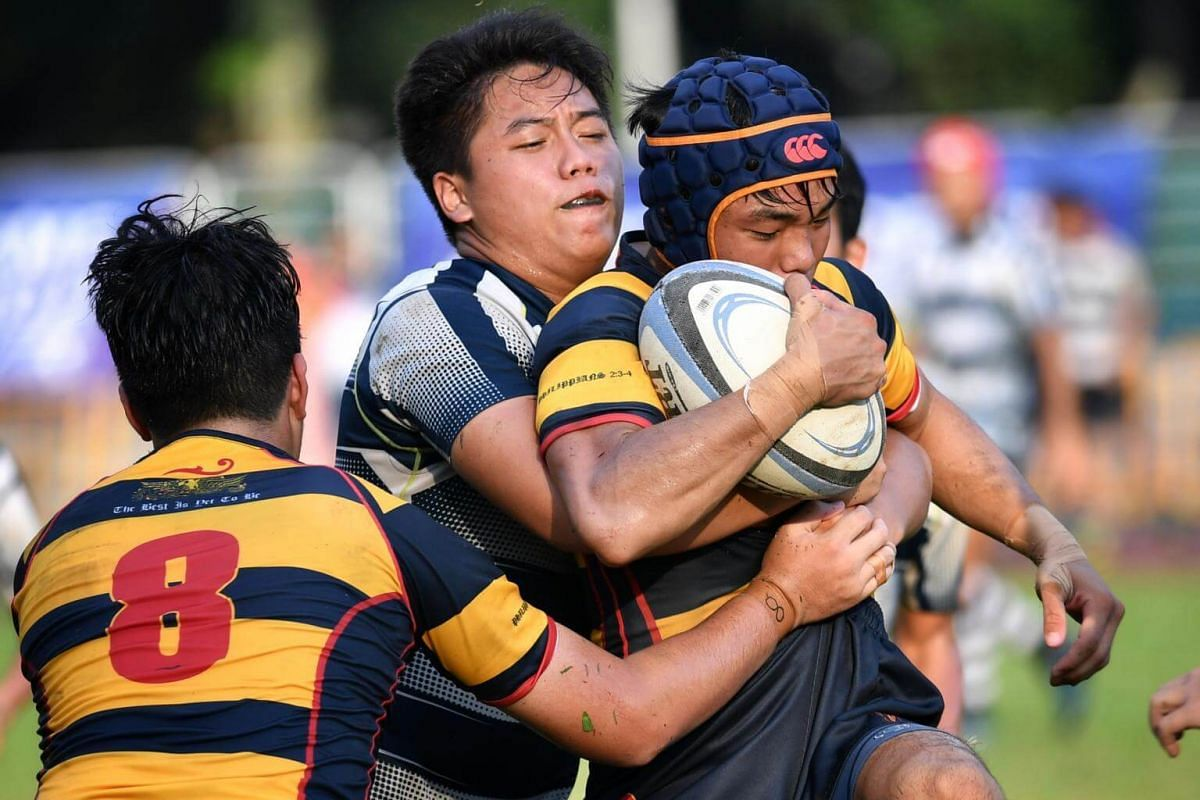 An ACS(I) rugby player is tackled by his opponent in the B division Boys Rugby Final.