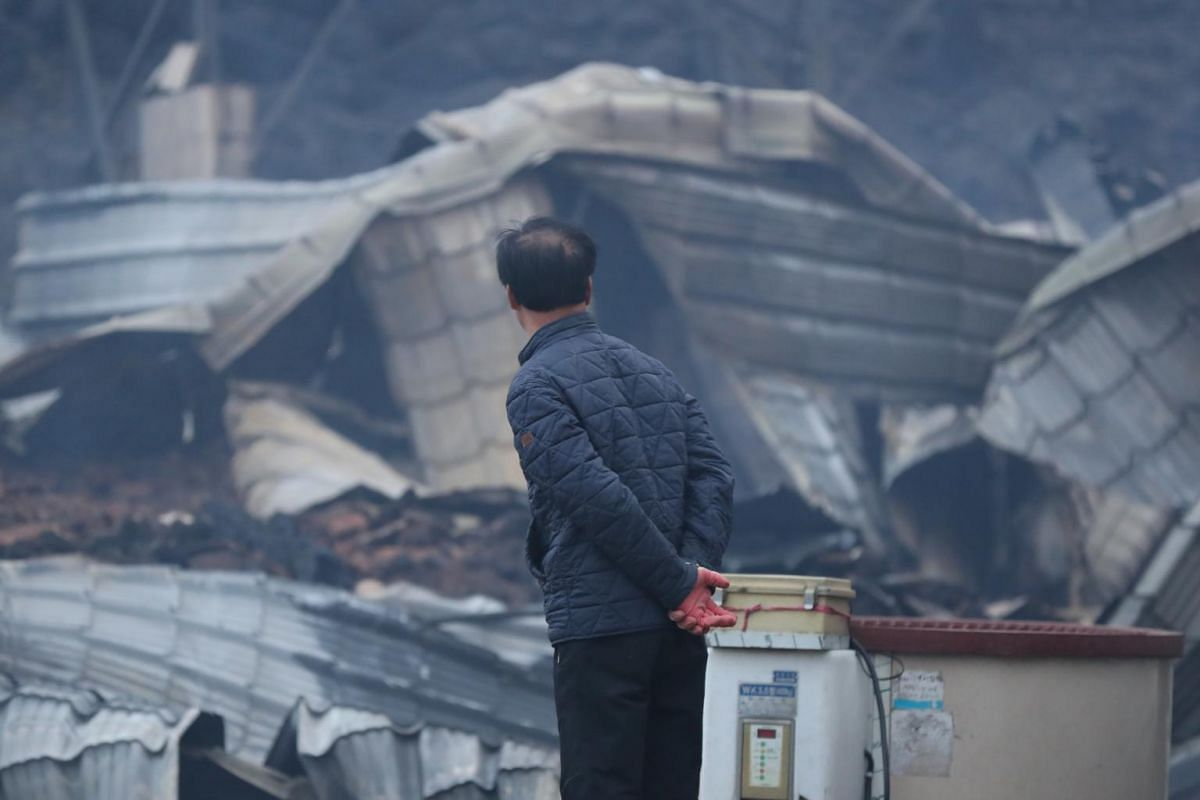 A resident looks at a gutted house after a massive fire engulfed the area, in Sokcho, South Korea, on April 5, 2019.