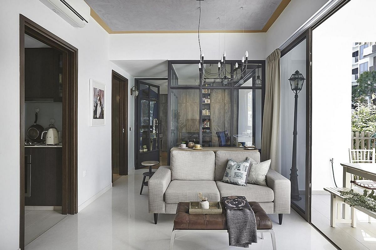 To create visual spaciousness and openness in the apartment of civil servant Cheong Mei Xi, tall glass panels in black frames instead of concrete walls separate the master bedroom from the living room (above).