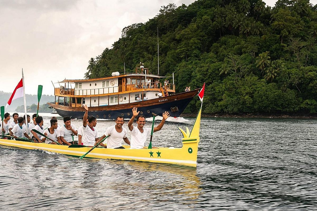 A kora kora races the Rascal, a phinisi yacht, out of the harbour at Banda Neira. Traditionally a war boat, the kora kora is now used for ceremonial purposes and in an annual race.