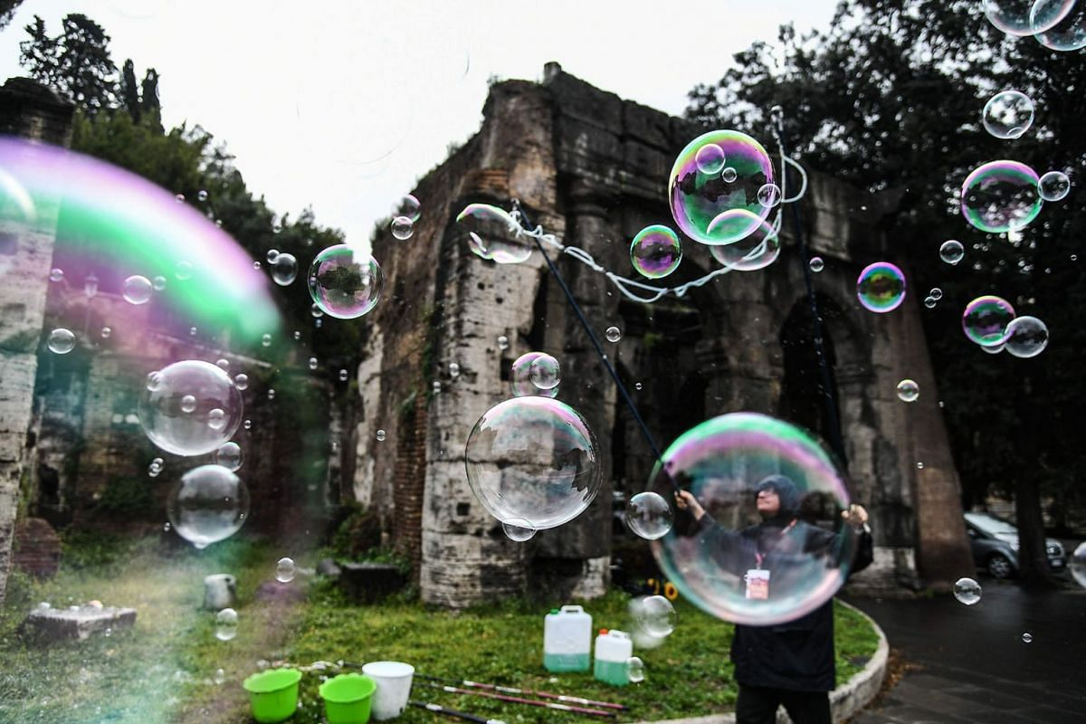 A man blows soap bubbles for tourists on April 7, 2019 in Rome. PHOTO: AFP