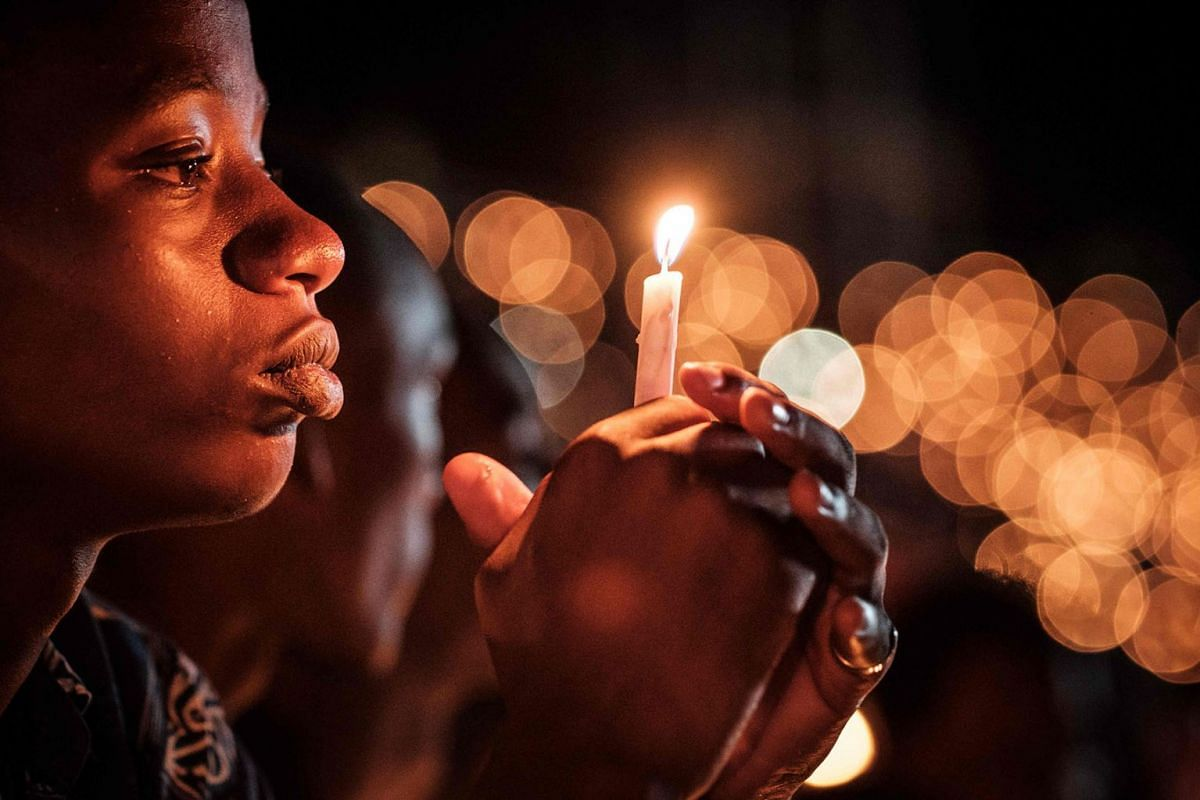 A person holds a candle during a night vigil and prayer at the Amahoro Stadium as part of the 25th Commemoration of the 1994 Genocide, in Kigali, Rwanda, on April 7, 2019. PHOTO: AFP