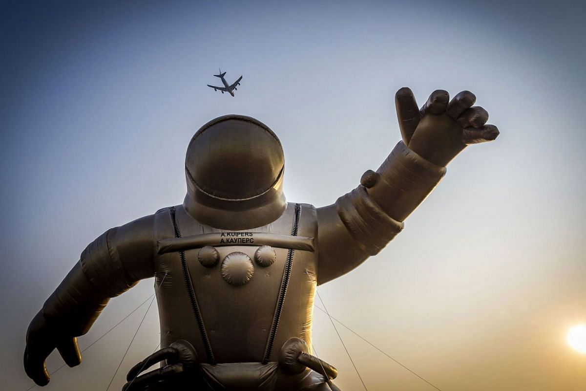 A airliner flies high above a giant gold-colored inflatable astronaut representing Dutch astronaut Andre Kuiper in his astronaut gear to mark the start of the fifth National Museum Week in Sassenheim, on April 8, 2019. PHOTO: AFP