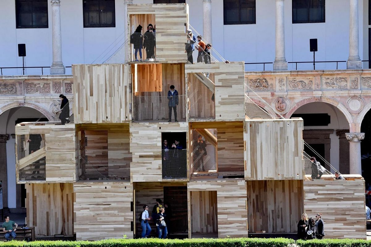 "Visitors climb on the installation ""Multiply Milano"" by Waugh Thistleton Architects, a modular structure composed by 16 cubes mads with crsoo laminated timber, part of the Fuori Salone Milan Design Week at the Statale Unuversity in Milan, Italy, 08"