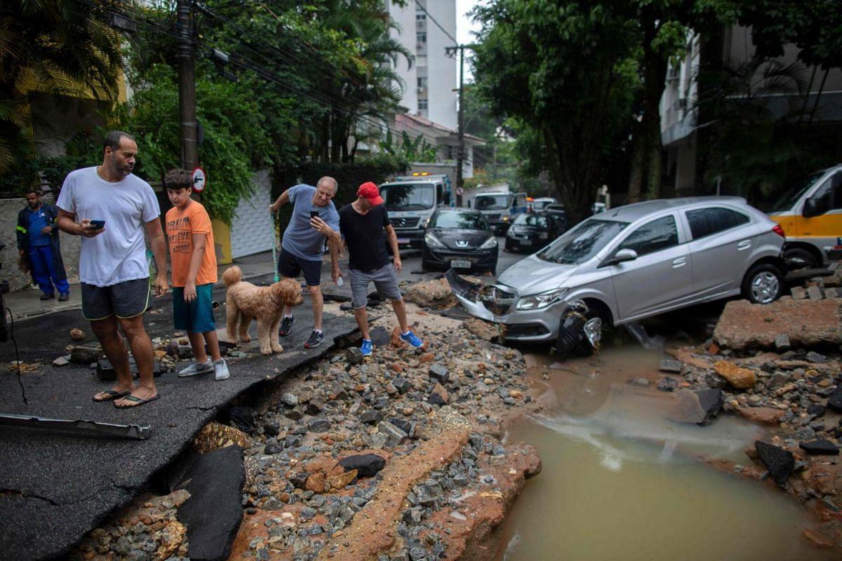 People look at the damage at Jardim Botanico neighbourhood in Rio de Janeiro, on April 9, 2019.