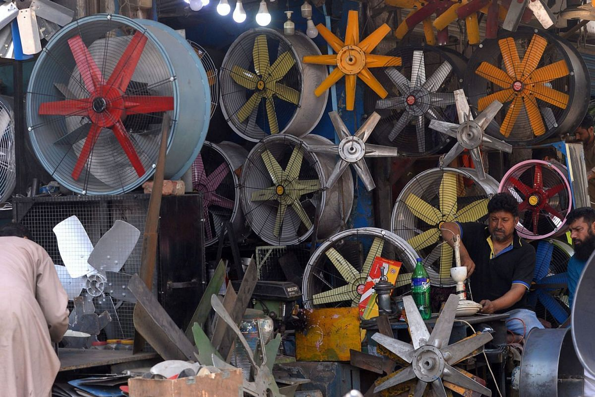 A Pakistani man repairs a fan at his workshop in Lahore on April 9, 2019. PHOTO: AFP