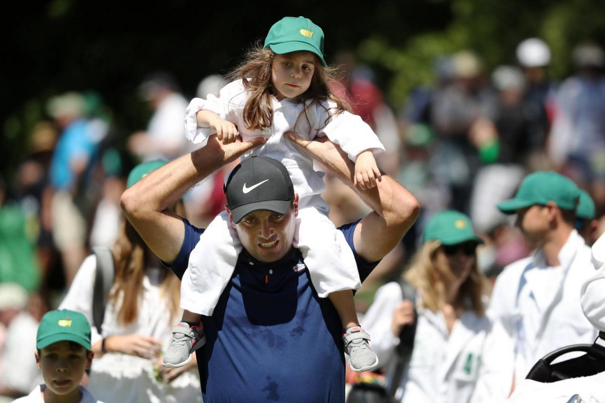 Francesco Molinari of Italy walks up the fifth hole with his daughter Emma during the Masters golf tournament's Par 3 Contest at the Augusta National Golf Club in Augusta, on April 10, 2019.