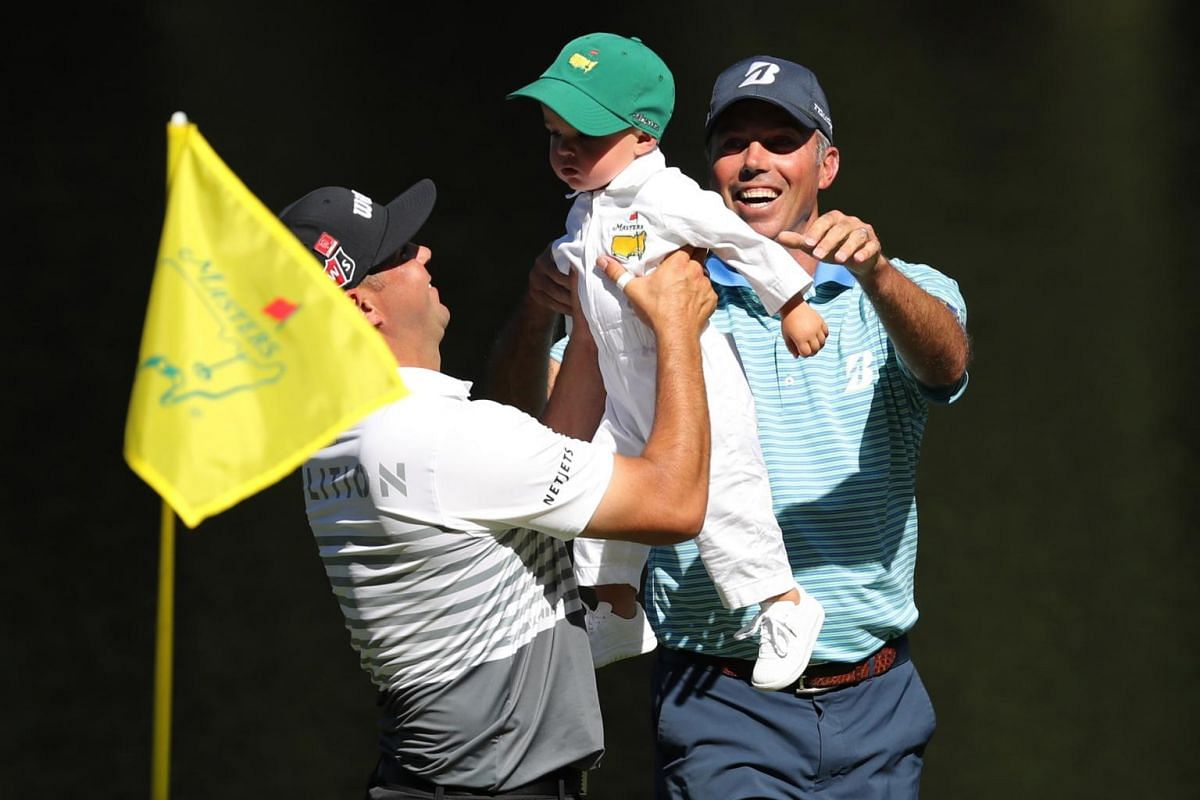 Gary Woodland of the United States lifts up his son Jaxson, as Matt Kuchar looks on, on the ninth hole during the Masters golf tournament's Par 3 Contest at the Augusta National Golf Club in Augusta, on April 10, 2019.