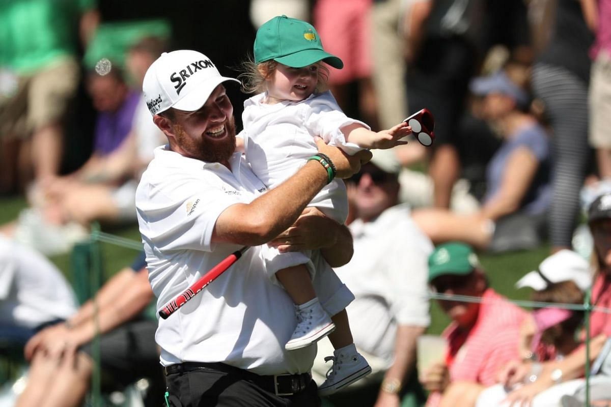 Shane Lowry of Ireland carries his daughter Iris during the 2019 Masters golf tournament's Par 3 Contest at the Augusta National Golf Club in Augusta, on April 10, 2019.