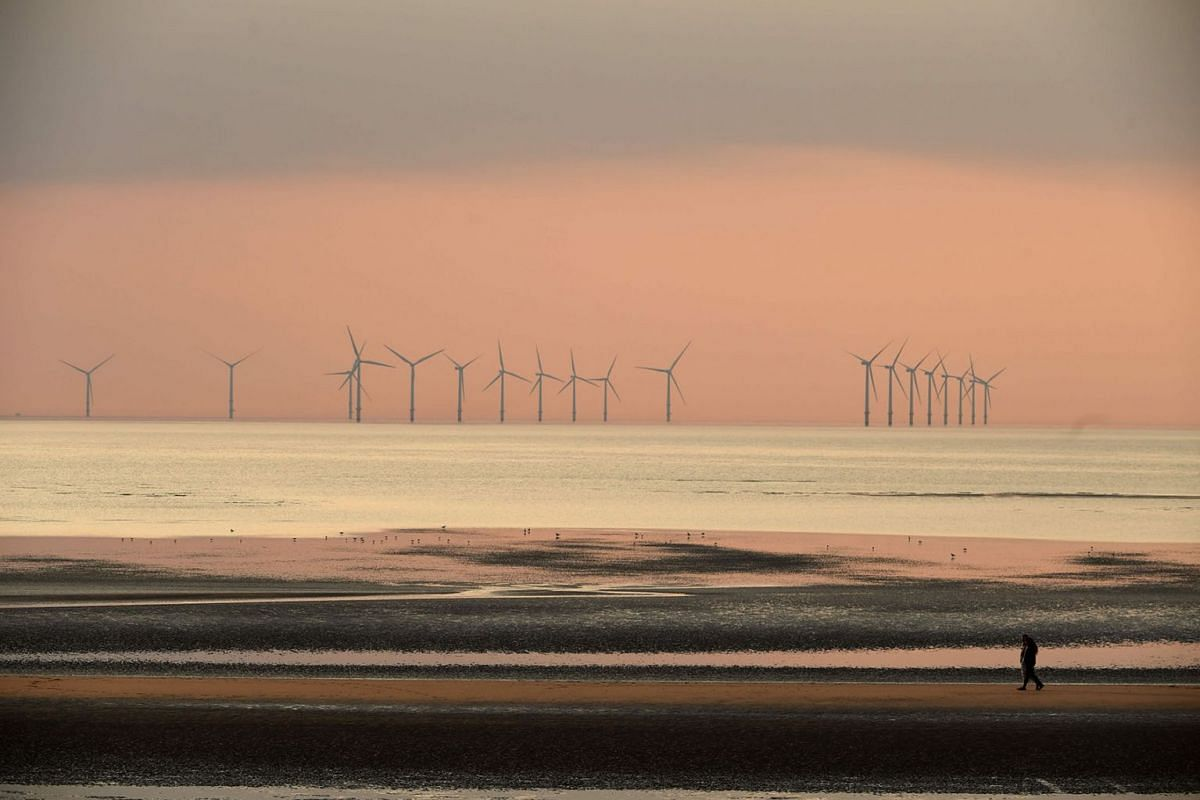 People walk on the beach at New Brighton, north west England at sunset on April 11, 2019, with the Burbo Bank wind farm on the Irish Sea in the background. PHOTO: AFP