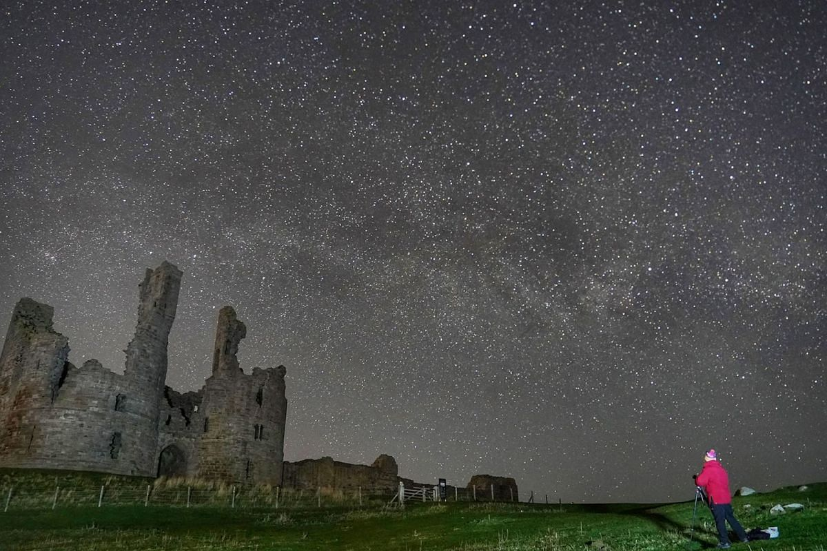 A man stands with his equipment to photograph the milky way over Dunstanburgh Castle, 11 April 2019, England, Northumberland. PHOTO: PA WIRE VIA DPA