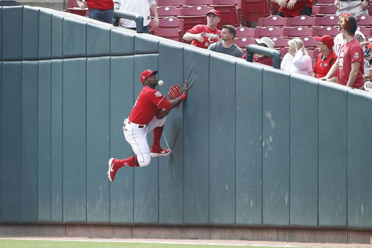 Yasiel Puig #66 of the Cincinnati Reds tries to catch the ball against the right field wall in foul territory in the first inning against the Miami Marlins at Great American Ball Park on April 11, 2019 in Cincinnati, Ohio. PHOTO: GETTY IMAGES/AFP