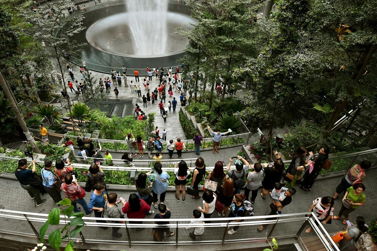 Visitors taking photographs of the HSBC Rain Vortex, the world's tallest indoor waterfall at 40 metres high and the nucleus of Jewel Changi Airport.