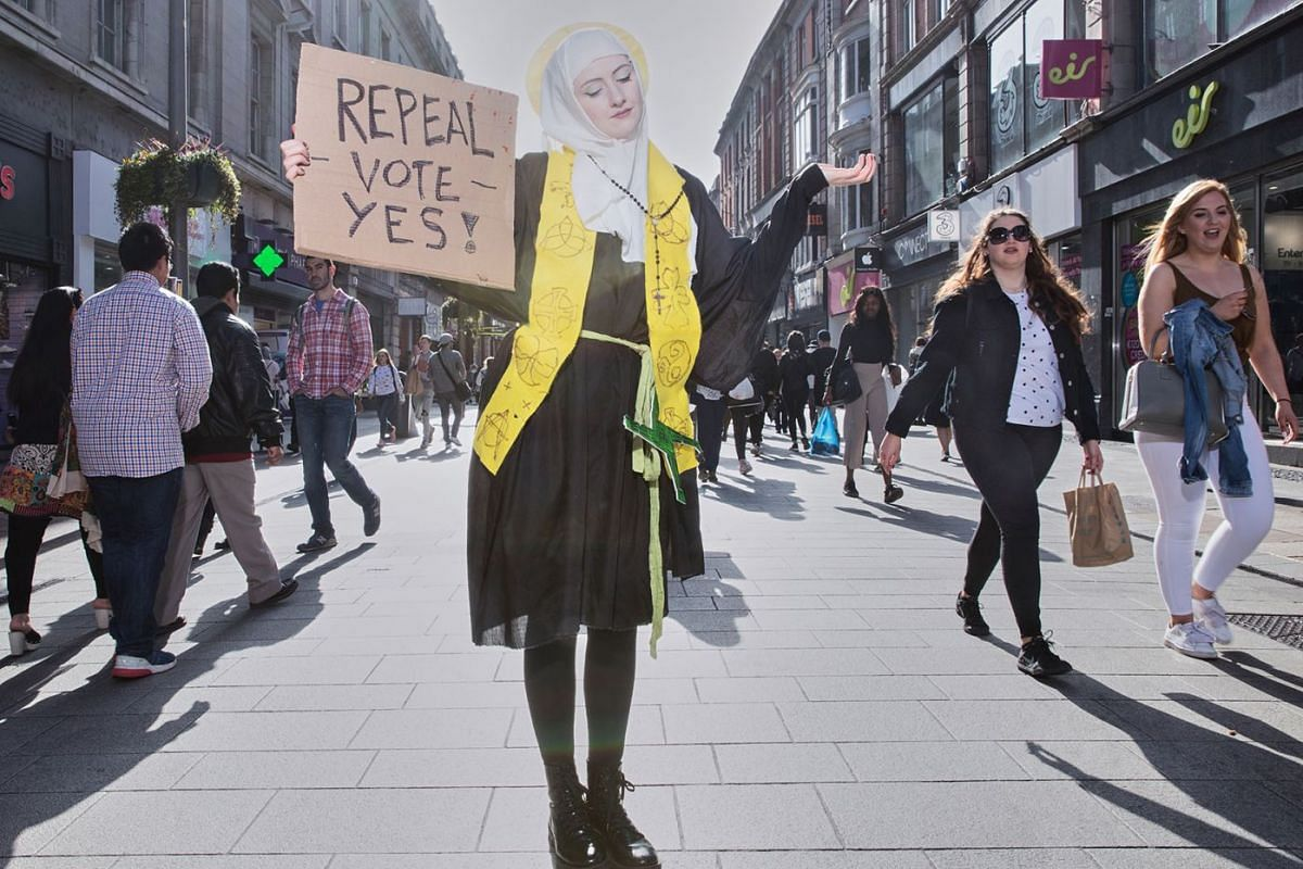 Abortion law reform campaigner Megan Scott, dressed as St Brigid, Ireland's female patron, poses for a photograph at Dublin's main shopping street on April 21, 2018.
