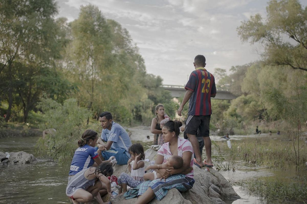 Families relax beside the Rio Novillero in Mexico, when the caravan takes a rest day near Tapanatepec.