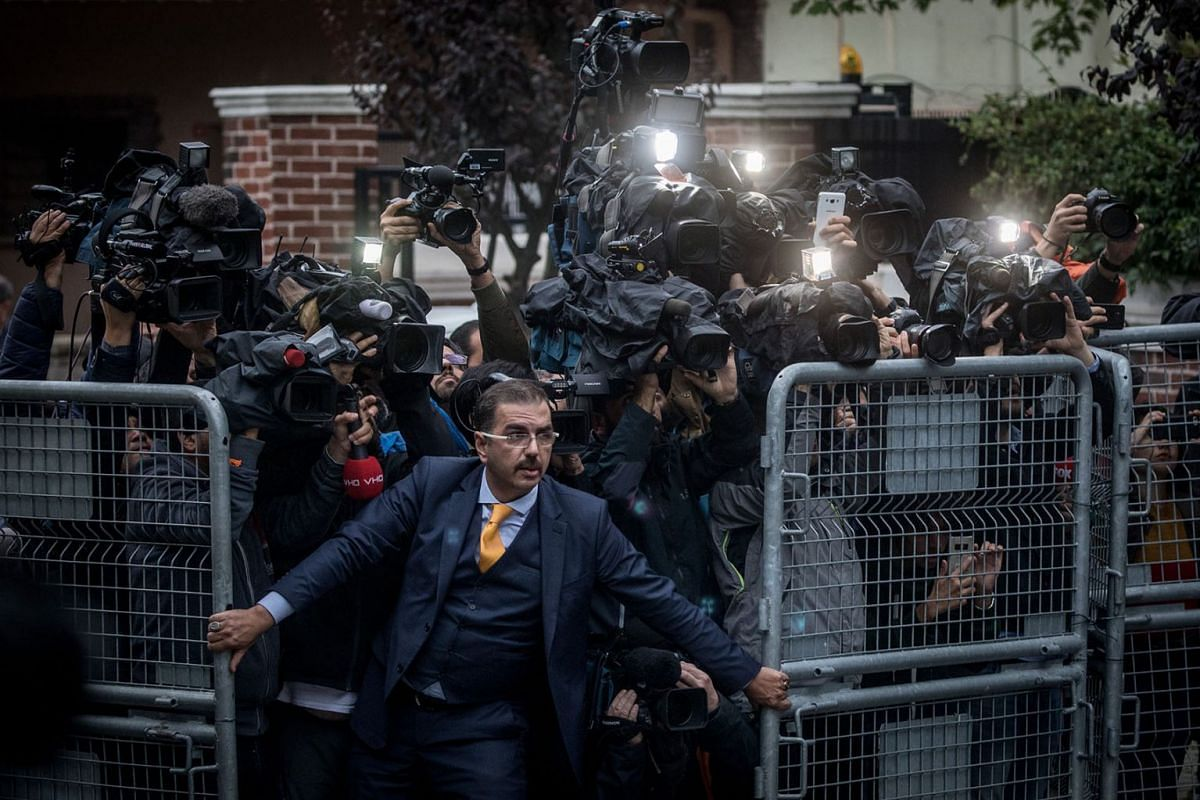 An unidentified man tries to hold back the press as Saudi investigators arrive at the Saudi Arabian Consulate in Istanbul, amid a growing international backlash over the disappearance of journalist Jamal Khashoggi.