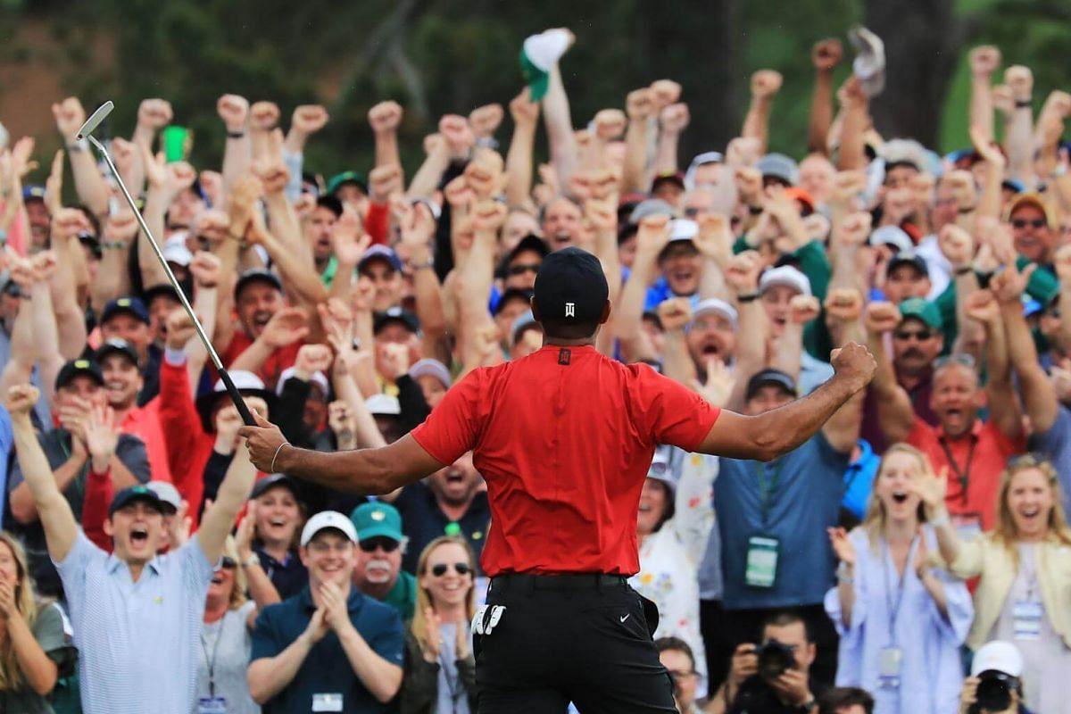 Patrons cheer as Tiger Woods celebrates after sinking his putt on the 18th green to win the 2019 Masters.