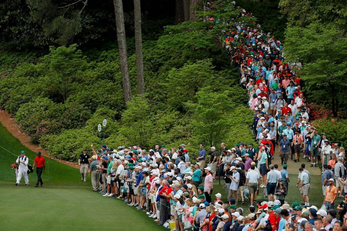 Tiger Woods walks onto the sixth hole as patrons gather during the final round of the 2019 Masters.