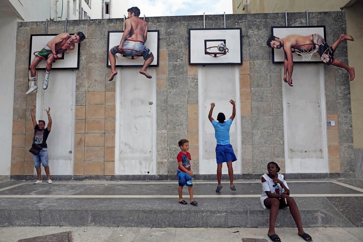 People interact with an installation by Spanish artists Martin and Sicilia during the 13th Havana Biennial arts event, in Havana, Cuba, on April 12, 2019.