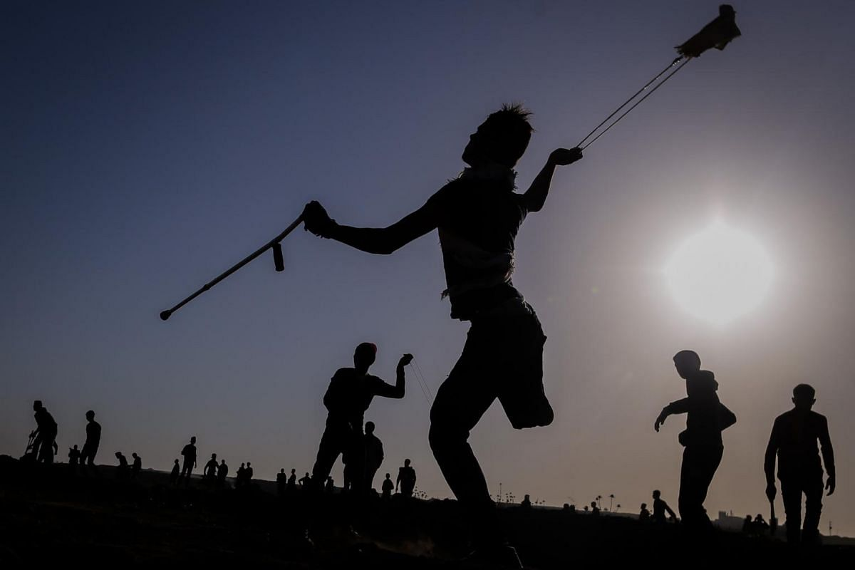 A Palestinian protester uses a sling to hurl stones at Israeli security forces during clashes along the Israel-Gaza border in Palestinian Territories, Gaza City, on April 12, 2019.
