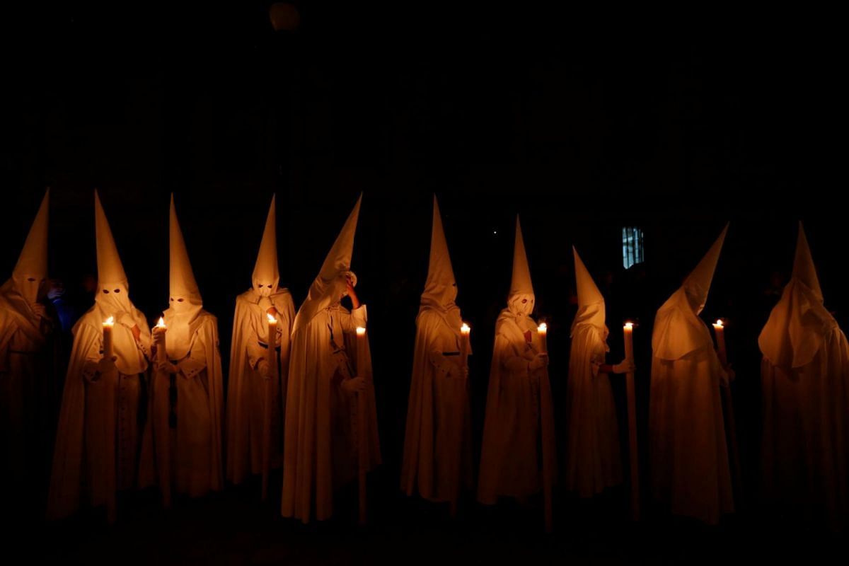 Penitents of La Paz (The Peace) brotherhood take part in a procession during Holy Week in the Andalusian capital of Seville, Spain, on April 14, 2019.