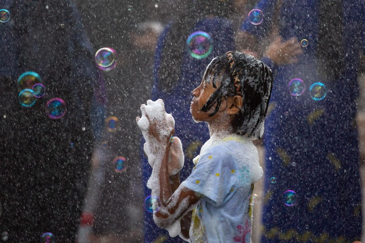 A girl plays with soap suds during celebrations for the Thingyan festival, also known as the Buddhist New Year, in Yangon, Myanmar, on April 13, 2019.