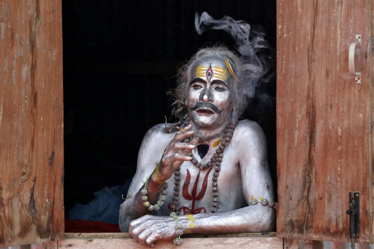 A devotee smokes as he waits to perform during the annual Hindu festival of Gajan on the outskirts of Agartala, India, on April 13, 2019.