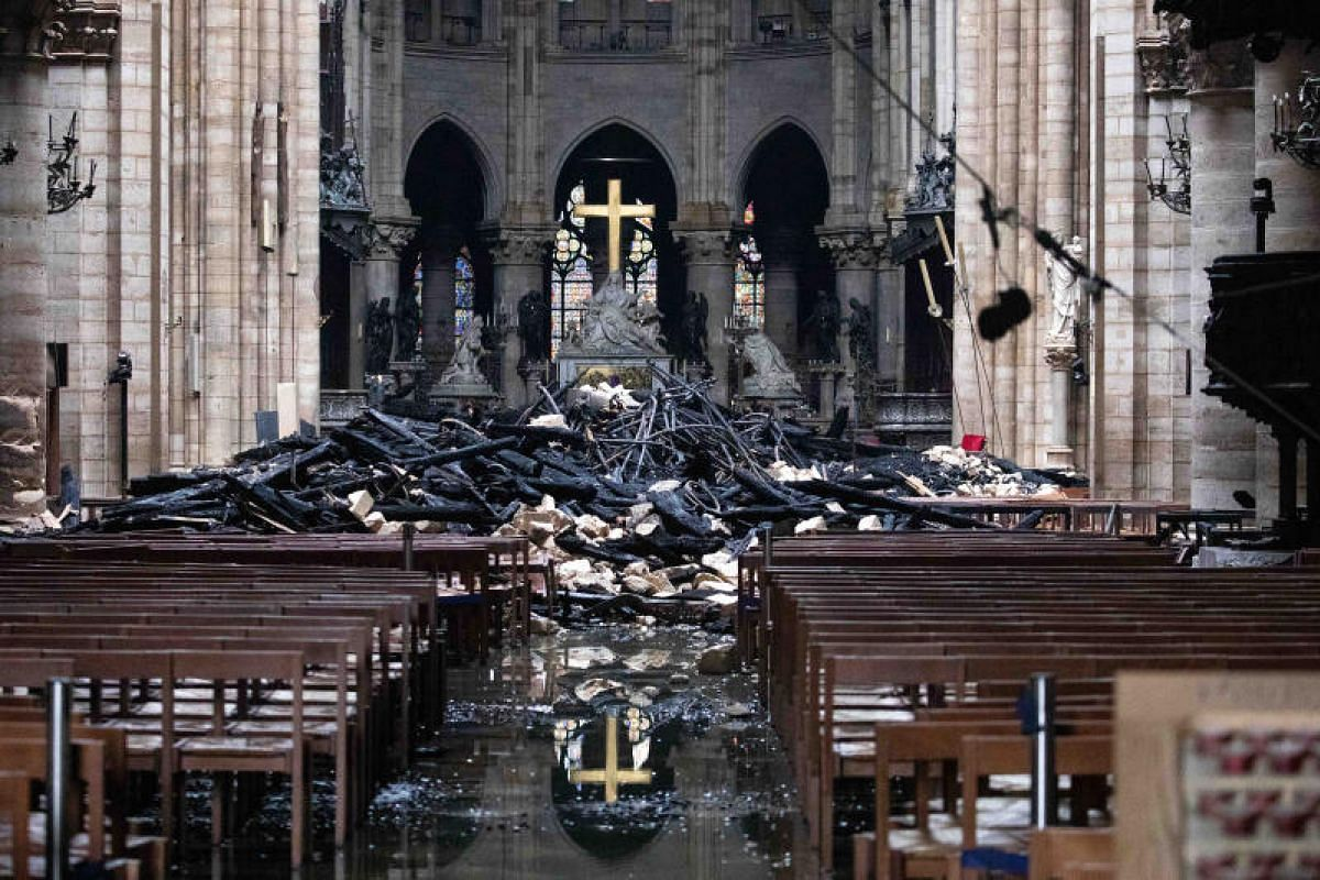 Fallen debris from the burnt out roof structure sits near the altar inside Notre Dame Cathedral in Paris, France, on April 16, 2019.