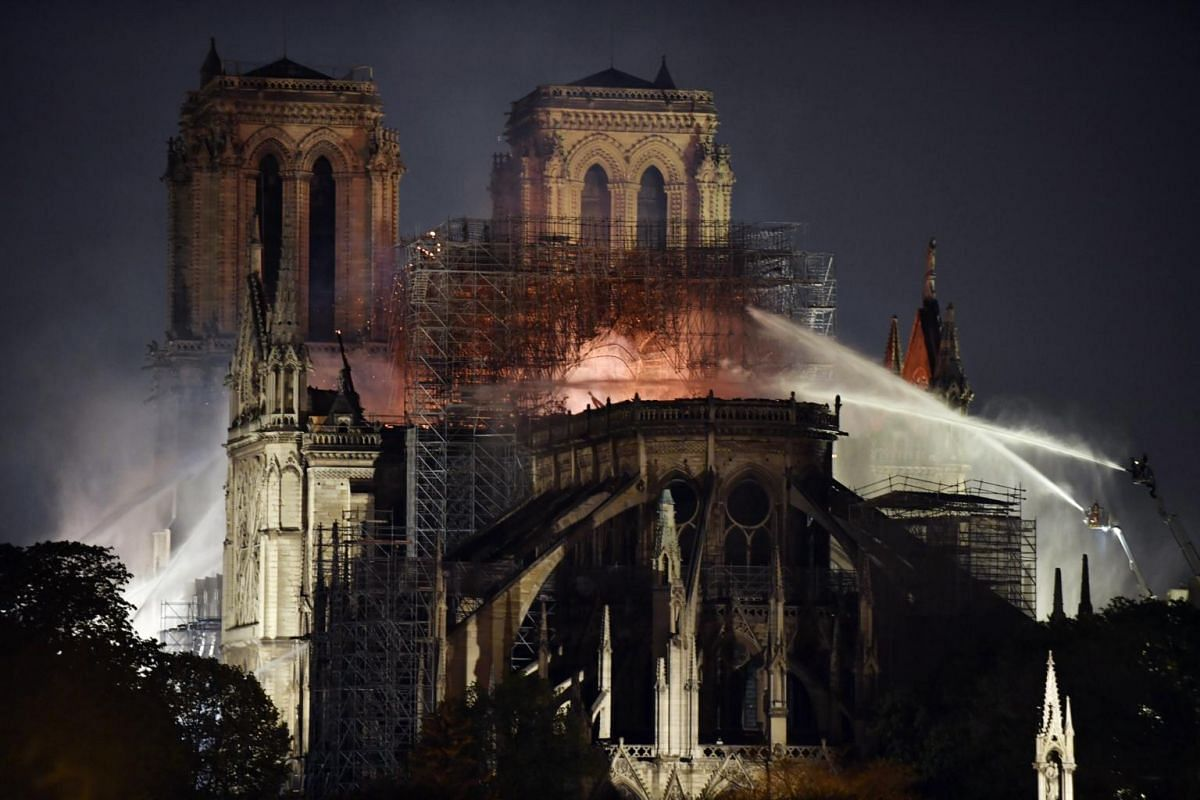 French firemen spray water to extinguish a fire as flames burn the roof of the Notre Dame Cathedral in Paris, on April 15, 2019.