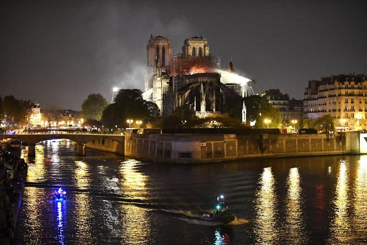 French firemen spray water to extinguish a fire as flames burn the roof of the Notre Dame Cathedral in Paris, on April 15, 2019. One firefighter was seriously injured – the only reported casualty.