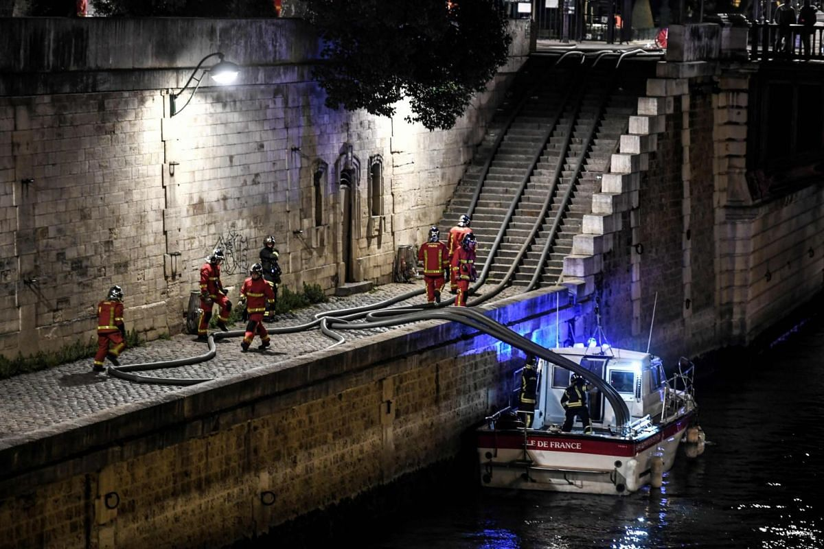Firefighters assemble their hoses as they gather at the River Seine near Notre Dame de Paris Cathedral as flames engulf the roof of the cathedral, on April 15, 2019.