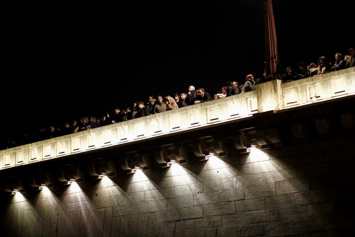 Thousands of onlookers line bridges over Seine and along its embankments to look at Notre Dame Cathedral after it suffered heavy damage from a fire in Paris on April 15, 2019