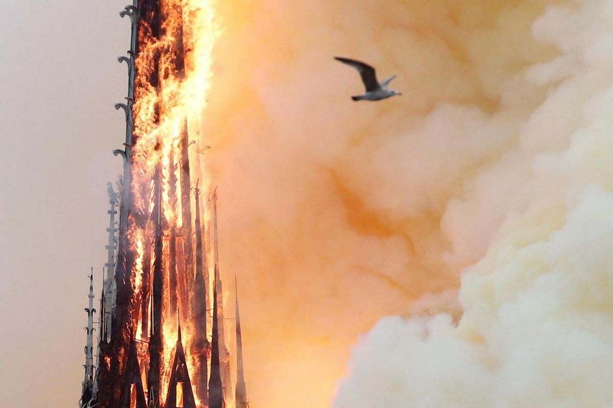 Smoke billows as fire engulfs the spire of Notre Dame Cathedral in Paris, France, on April 15, 2019.
