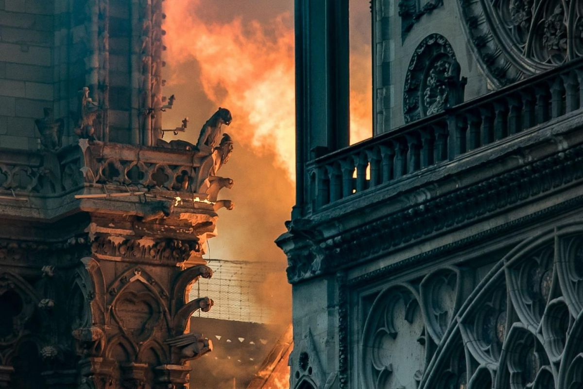Flames and smoke billow around the gargoyles decorating the roof and sides of the Notre Dame Cathedral in Paris, on April 15, 2019.