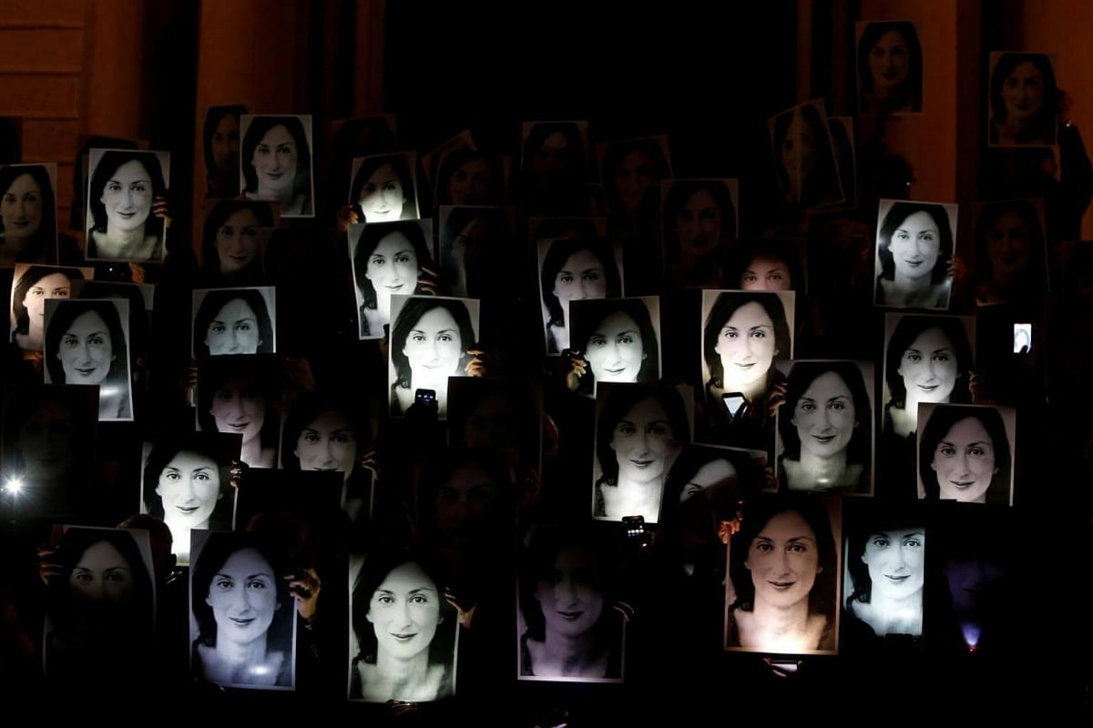 People holding up photos of anti-corruption journalist Daphne Caruana Galizia during a protest marking 18 months since her assassination, outside the office of Prime Minister Joseph Muscat at Auberge de Castille in Valletta, Malta, on April 16, 2019.