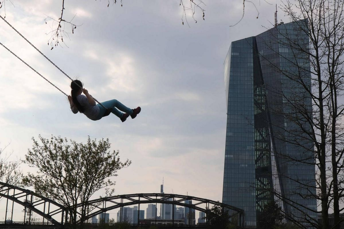 A child swings in a park in front of the European Central Bank headquarters in Frankfurt, Germany, on April 16, 2019.