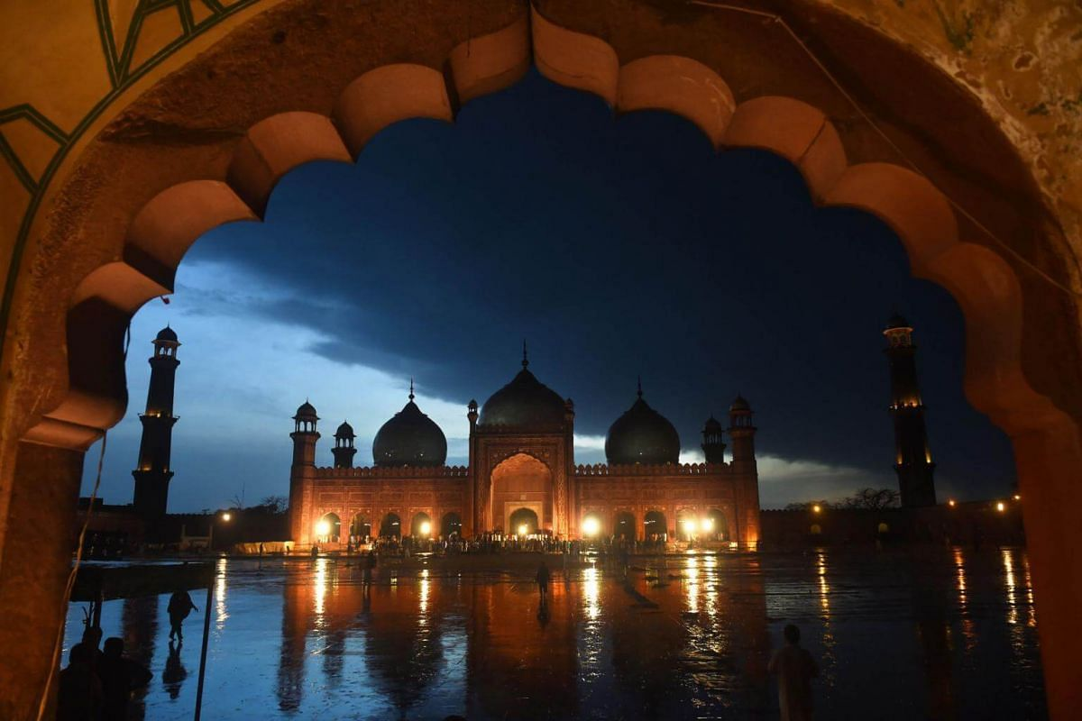 People arriving to pray at the historical Badshahi Mosque during heavy rain in Lahore, Pakistan, on April 16, 2019.