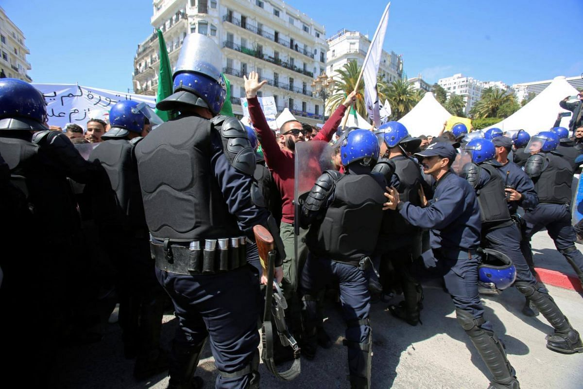 Police confront students as they take part in a protest seeking the departure of the ruling elite in Algiers, Algeria, on April 16, 2019.