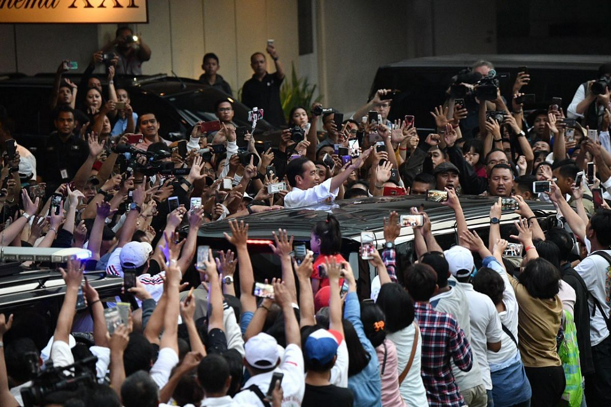 Supporters cheer as President Joko Widodo leaves Djakarta Theater in Jakarta where he meets leaders of political parties supporting his campaign.