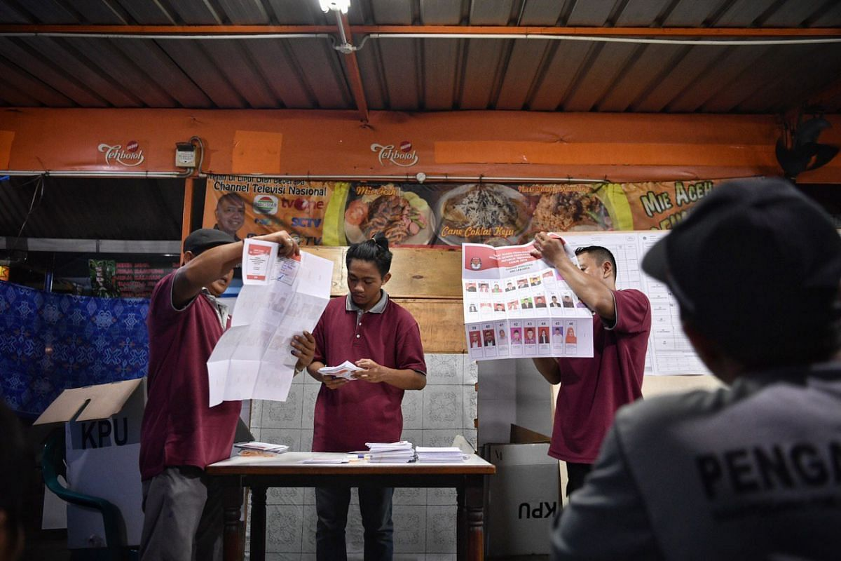 Polling station committee members count votes as witnesses representing political parties and an election watchdog official look on at a polling station in Bendungan Hilir in central Jakarta.