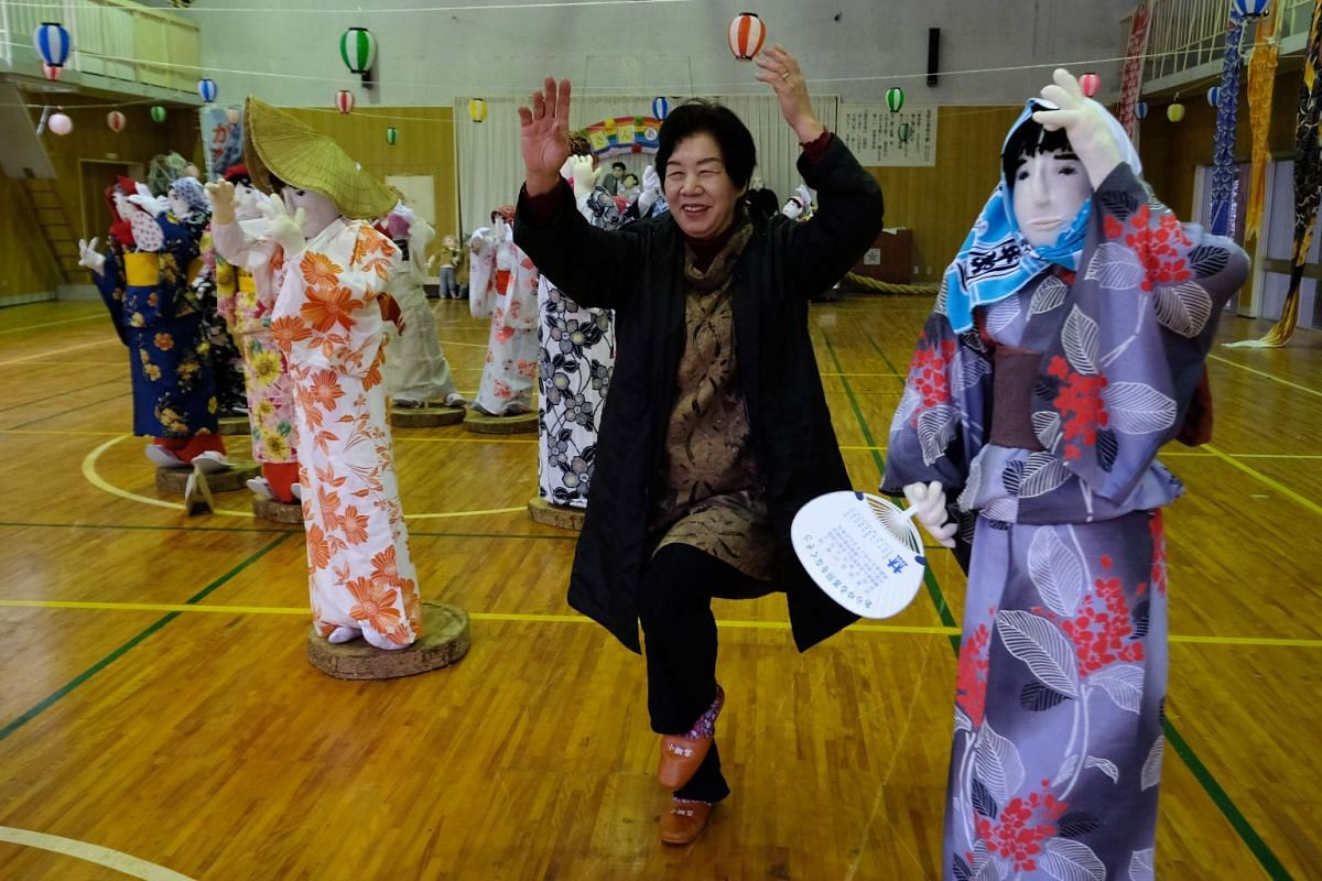 Nagoro resident Tsukimi Ayano posing with life-sized dolls at an elementary school that closed seven years ago, as there was no one left to teach.