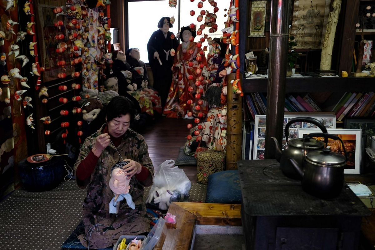 Madam Tsukimi Ayano, 69, sewing the head of a life-sized doll at her house in Nagoro.